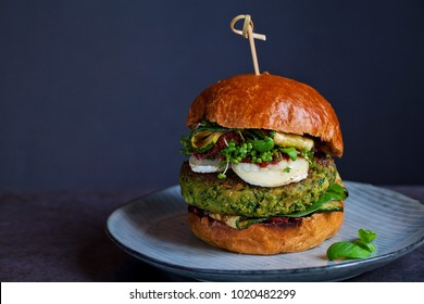 Vegetarian burger made of green pea, butter beans and spinach  with sundried tomato pesto and grilled courgette