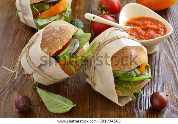 Vegetarian burger wrapped in paper and tied with twine with sauce