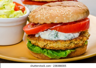 Vegetarian chickpea burger, tomato and dip of herbs, garlic and yogurt and salad with cherry tomatoes