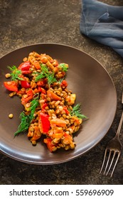 Vegetarian chick-pea, lentil, pepper, tomatoes and carrots salad in a plate on dark background. Selective focus.