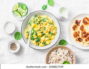 Vegetarian chickpea, spinach, potato curry, naan flatbread and wild rice on white background, top view. Indian healthy food concept