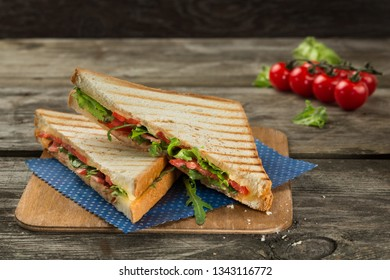 Vegetarian club sandwich with tomato, cheese, arugula and green salad on the wooden background