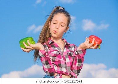 Vegetarian concept. Kid girl hold red and green peppers sky background. Child presenting kinds of pepper. Kid hold ripe pepper harvest. Fall harvest homegrown vegetables. Which pepper would you pick.