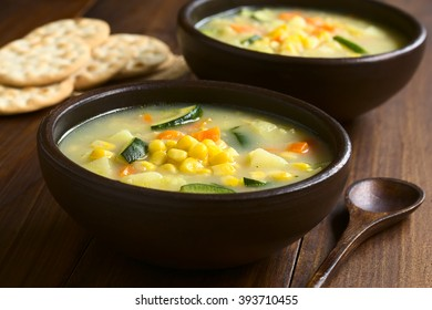 Vegetarian corn and courgette chowder served in rustic bowls, saltine cracker in the back, photographed on dark wood with natural light (Selective Focus, Focus one third into the soup)