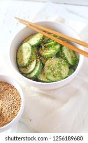 Vegetarian cuisine. Asian cucumber salad, sesame dressing on light background