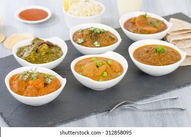 Vegetarian Curries - Selection of South Asian vegetarian curries in white bowls. Paneer Makhani, Palak Paneer, Aloo Matar, Baigan Bharta, Chilli Potatoes and Bhindi Masala.