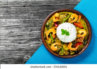 vegetarian curry with rice and prawns on a clay brown dish on a table mat on a old wooden background top view