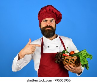 Vegetarian diet concept. Cook with confused face in burgundy uniform holds vegetables in wicker bowl. Man with beard on blue background. Chef points at lettuce, tomato, pepper and mushrooms.