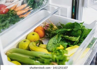 Vegetarian diet. Plastic free bananas,salad, spinach, celery, apples, orange in fridge. Zero waste grocery shopping. Fresh vegetables in opened drawer in refrigerator.  Food delivery