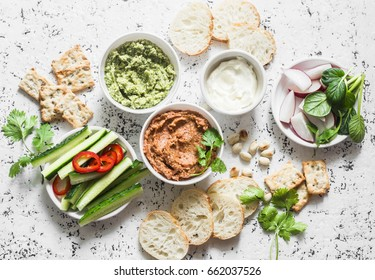 Vegetarian dip table. Eggplant, harissa, walnuts dip, broccoli dip, soft tofu and fresh vegetables on a light background, top view. Flat lay