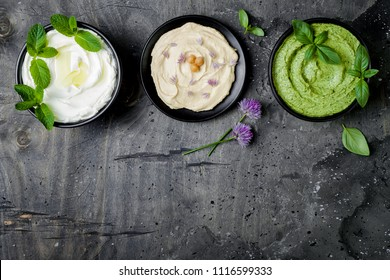 Vegetarian dip table. Yogurt sauce or labneh, hummus, herb hummus or pesto. Middle eastern meze snacks set. Copy space, flat lay, overhead