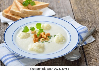 Vegetarian dish: Delicious cauliflower cream soup topped with fresh croutons and served with crisp toast