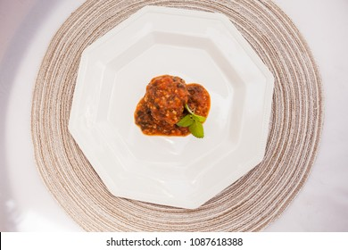 Vegetarian dish of millet meatballs with spinach in tomato sauce, ambient light.