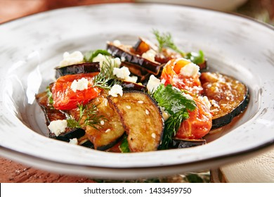 Vegetarian Eggplant Salad with Baked Aubergine, Cherry Tomatoes and Cilantro Close Up. Macro Photo of Grilled Eggplants and Cottage Cheese with Fresh Dill, Parsley, Sesame Seeds and Spicy Oil