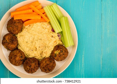 Vegetarian Falafels With Moroccan Style Houmous Carrots and Celery On A Blue Wooden Background