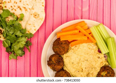 Vegetarian Falafels With Moroccan Style Houmous Carrots and Celery On A Pink Wooden Background