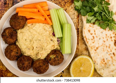 Vegetarian Falafels With Moroccan Style Houmous Carrots and Celery On A Distressed Oven or Baking Tray