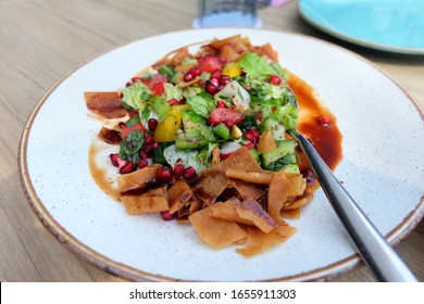 Vegetarian fattoush salad lunch. The key ingredient in this middle eastern dish is the toasted pita bread which is mixed with healthy vegetables, herbs and a dressing made with lemon and sumac.