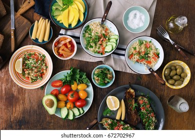 Vegetarian food concept. Set of healthy vegetarian food, salad with bulgur porridge and vegetables, stuffed eggplant, vegetables, mango, avocado and snacks on a wooden table, top view