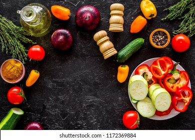 Vegetarian food concept. Set of vegetables for stew. Squash, bell pepper, tomato, spices, oil on black background top view space for text