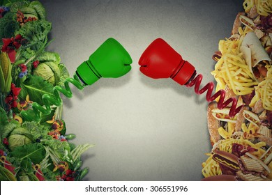 Vegetarian food fighting unhealthy junk food with boxing gloves punching each other. Diet battle nutrition concept.