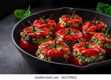 Vegetarian food: Mediterranean style baked tomatoes stuffed with feta cheese, spinach and herbs