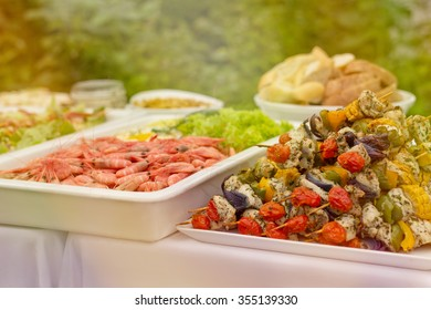 Vegetarian food on outdoor romantic wedding party in the old greenhouse with the wild nature in the background - fresh shrimps and rainbow vegetarian skewers