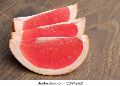 Vegetarian food as a sliced fresh pink grapefruit on a wooden background