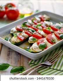 Vegetarian food, Zucchini with the addition of tomatoes, mozzarella, basil and olive oil (caprese salad) in a ceramic baking dish, close-up. Stuffed courgettes ready for baking