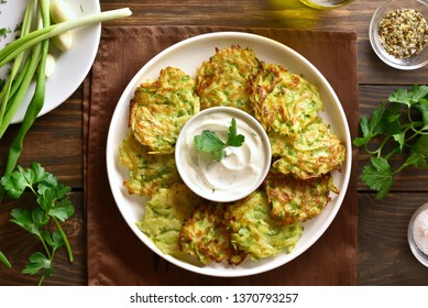 Vegetarian food. Zucchini fritters, thin pancakes and sauce on white plate over wooden table. Top view, flat lay
