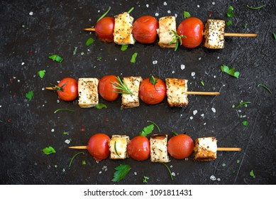 Vegetarian grilling. Vegetarian skewers with halloumi cheese and tomatoes on black background.