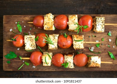 Vegetarian grilling. Vegetarian skewers with halloumi cheese and tomatoes on wooden background.