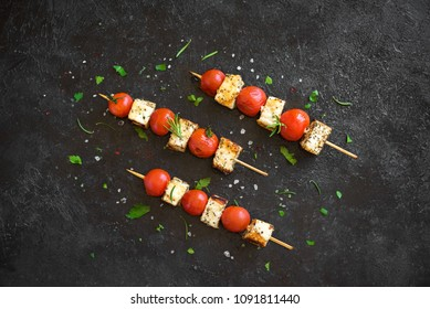 Vegetarian grilling. Vegetarian skewers with halloumi cheese and tomatoes on black background, copy space.
