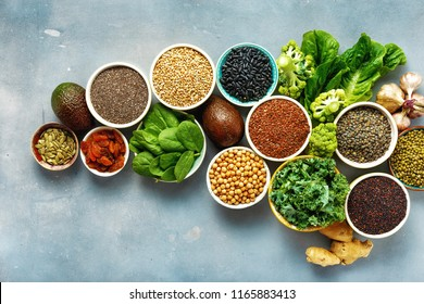 Vegetarian healthy food concept. Set raw seeds, cereals, beans, superfoods and green vegetables on blue stone background top view flat lay