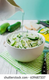 vegetarian Healthy food, light, low calorie fitness salad of fresh cucumbers, cabbage and dill with olive or sunflower oil, spices and salt on a light wooden background