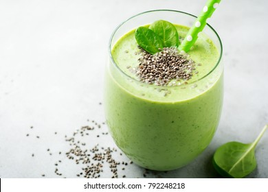Vegetarian healthy green smoothie from avocado, spinach leaves, apple and chia seeds on gray concrete background. Selective focus. Space for text.