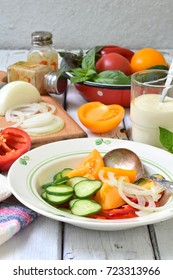 Vegetarian healthy salad with fresh ripe summer vegetables: tomato, cucumber,  pepper and onion on light wooden background