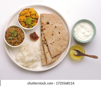 vegetarian Indian thali or Indian home food with lentil dal, cauliflower curry, roti or Indian flat bread, ghee butter, lemon pickle, rice, curd or yogurt