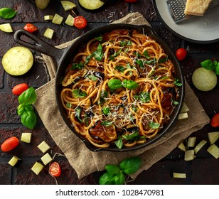 Vegetarian Italian Pasta Spaghetti alla Norma with eggplant, tomatoes, basil and parmesan cheese in rustic skillet pan.