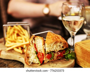Vegetarian Italian Style Red Pepper Ciabatta Bread Sandwich with a Glass of White Wine On a Wooden Serving Board with Chips or Fries