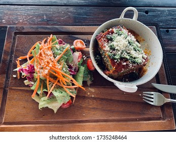 Vegetarian lasagna on a white plate and a salad on a wooden board and table. Fork and a knife. Vikasa Life Cafe in Ko Samui Top view