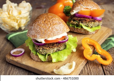 Vegetarian lentil burger with vegetables on wooden cutting board - healthy tasty vegetarian snack (food, lunch)