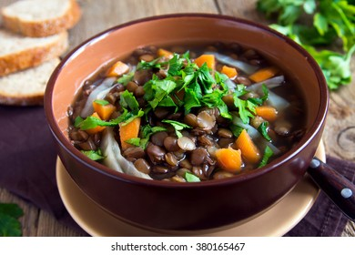 Vegetarian lentil soup (stew) with vegetables and parsley on rustic wooden background