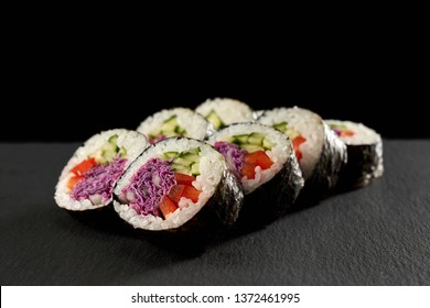 Vegetarian maki filled with cucumber or kappa, red paprika and violet cabbage. Veggie rolls wrapped in nori, served on black stone.