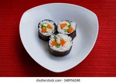 Vegetarian maki sushi rolls with rice, carrots, zucchini, green beans, tofu and nori seaweed in white dish on red background