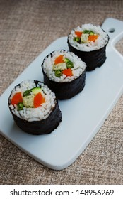 Vegetarian maki sushi rolls with rice, carrots, zucchini, green beans, tofu and nori seaweed in white dish on natural background
