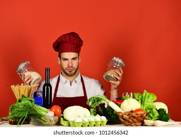 Vegetarian meal concept. Chef with serious face holds jars with porridge on red background. Man in cook hat and apron uses groats. Cook works in kitchen near table with vegetables and tools.