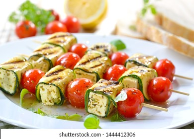 Vegetarian meal: Grilled marinated feta skewers with Greek cheese, zucchini,  cherry tomatoes and herbs