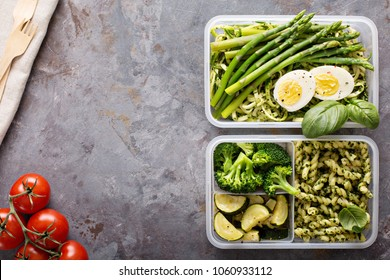 Vegetarian meal prep containers with eggs, zucchini noodles and pasta with green pesto sauce and vegetables