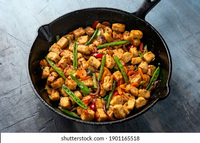 Vegetarian meat free mycoprotein pieces vegetable stir fry served in cast iron skillet frying pan